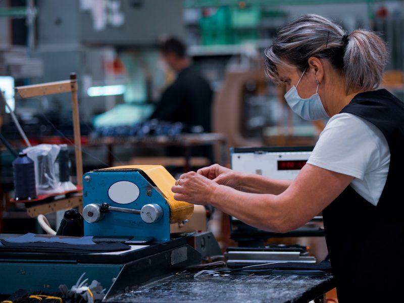 Shoe making process in footwear handmade  factory. Pandemic covid-19 virus.